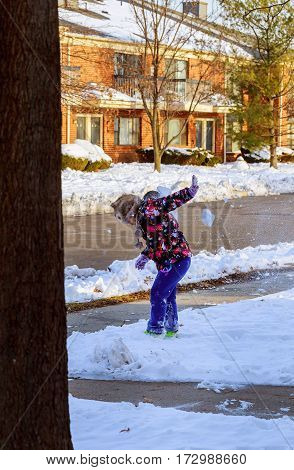 Little girl shoveling snow on home drive way. Child with shovel playing outdoors in winter season.
