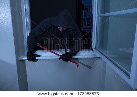 Burglar With A Crowbar Entering In A Room Through A Window