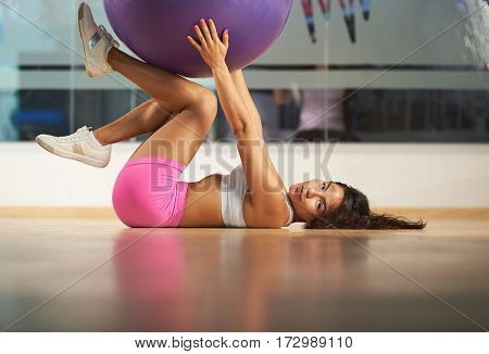 Young woman laying on fitness club flooor and hold fitball. Hispanic girl with fitball