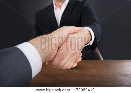 Close-up Of A Two Businessmen Shaking Hands On Wooden Desk Against Gray Background