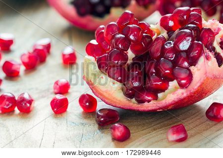 piece of red pomegranate on the wooden background with scattered grains
