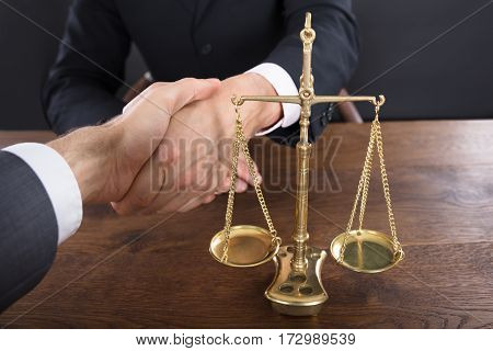 Close-up Of A Judge And Client Shaking Hands Near Justice Scale On Wooden Scale
