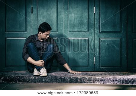 handsome lonely man in frustrated depression sitting alone on the floor. looking and touch at empty space nobody beside him. Concept of lonely sadness alone depressed and human problems.
