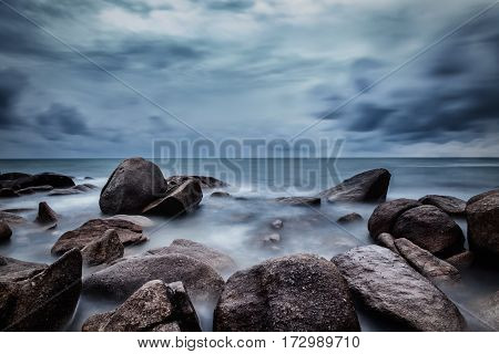 Dark rocks in a blue ocean under cloudy sky in a bad weather. Long exposure photography.