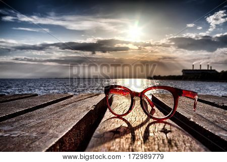 Beautiful spectacles on wooden bridge extended into the sea near the beach. with factory and sunset behind.