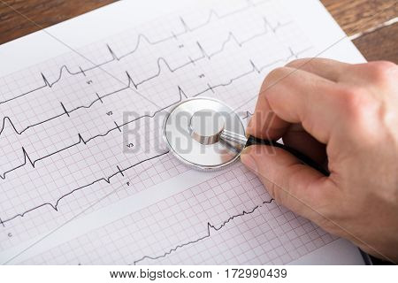 High Angle View Of Person Hand Using Stethoscope On Cardiogram Chart On Wooden Desk