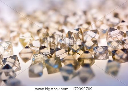 Collection of faceted natural transparent diamonds in macro with yellow reflection