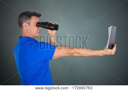 Matured Man With Hyperopia Eye Disorder Reading A Book Using Binocular On Gray Background