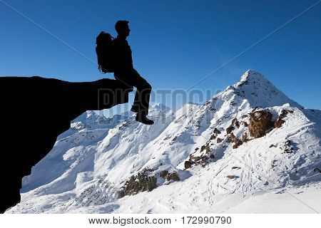 Silhouette Of A Man With Backpack Sitting At The Edge Of Cliff Exploring View