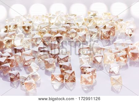 Collection of faceted natural transparent diamonds in macro with yellow reflection in the light background