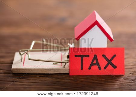 Tax Concept With House Model On Mousetrap At Wooden Desk