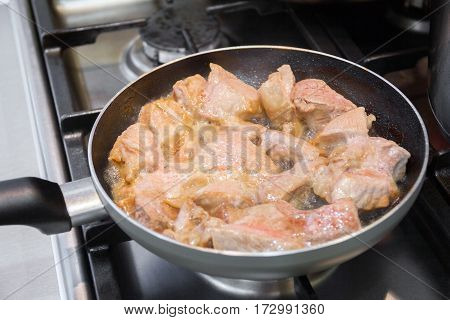 pieces of meat are fried on a frying pan