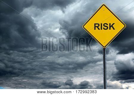 road warning sign with text risk in front of storm cloud background