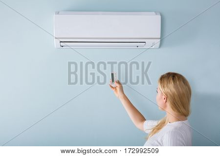 Young Woman Operating Air Conditioner With Remote Controller At Home