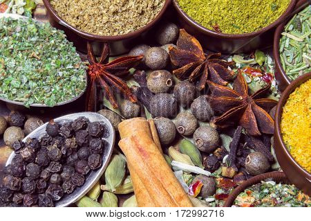 various spices in containers, in spoons and on a table as a background
