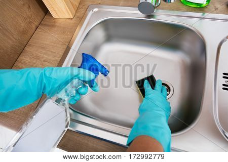 Close-up Of Person Hands Cleaning Kitchen Sink With Spray Bottle And Sponge