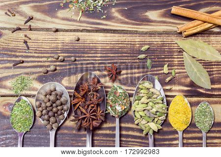 various spices in spoons on a wooden background