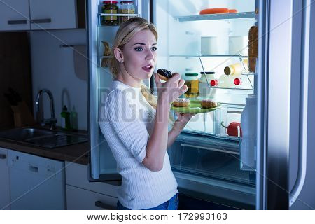 Young Woman Standing In The Kitchen Eating Donut Secretly From Fridge