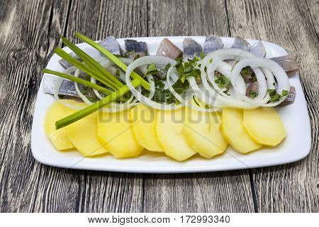 Dutch national appetizer, herring with onions.Tasty pieces of Icelandic herring with boiled potatoes and onions on the plate. National Icelandic snack Fat herring.