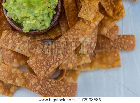 Texture of Homemade Chips with Guacamole in Top Left Corner and Copy Space in Right
