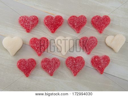 Three Rows of White and Red Gummy Hearts on Wooden Background