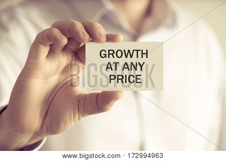 Businessman Holding Growth At Any Price Message Card