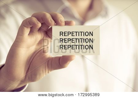 Businessman Holding Repetition, Repetition, Repetition Message Card