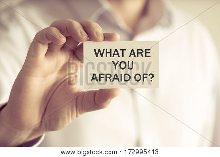 Businessman Holding What Are You Afraid Of ? Message Card