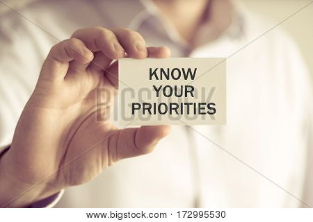Businessman Holding Know Your Priorities Message Card