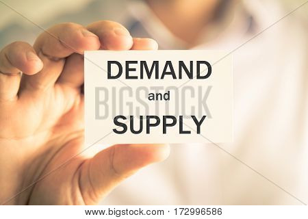 Businessman Holding Demand And Supply Message Card