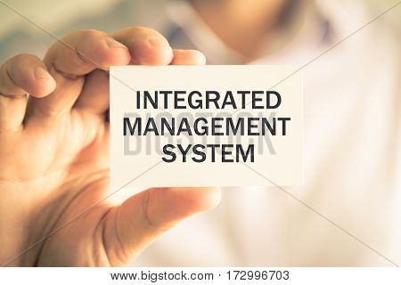 Businessman Holding Integrated Management System Message Card