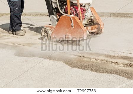 Construction worker cutting asphalt or concrete with saw blade, worker using protective shoes and gear