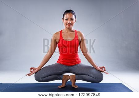 Yoga concept Pretty sporty indian woman smiling in doing yoga on concrete background