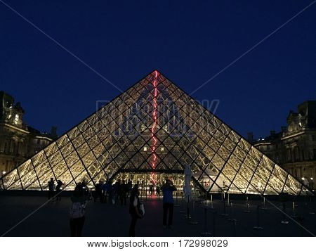 photo of Louvre Piramid at night with people