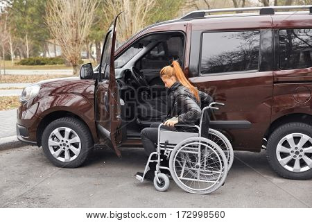 Young woman in a wheelchair next to her car