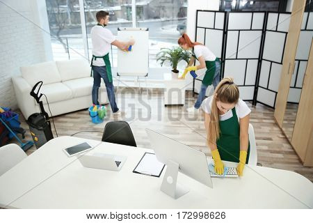 Team of cleaning service working at office