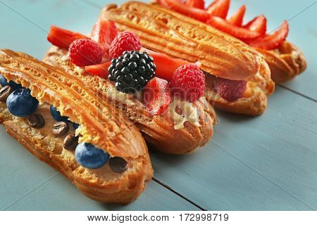 Delicious eclairs with berries on wooden tray