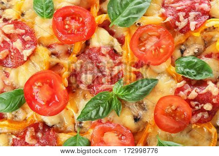 Close up view of tasty pizza with pepperoni, cheese, tomatoes, basil and salad pepper