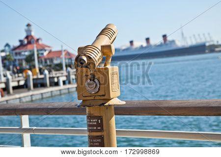 LONG BEACH, CALIFORNIA - February 14, 2017: Shoreline Village in Long Beach, CA. Telescope overlooking Long Beach harbor to the retired cruise ship, Queen Mary 2.