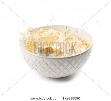 Corn flakes in bowl with milk splash on white background