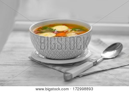 Bowl with vegetable soup on wooden table