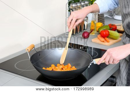 Woman mixing vegetables in pan at kitchen