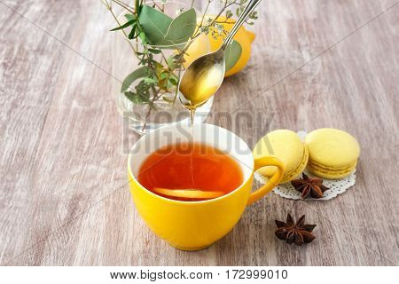 Pouring honey in to cup on wooden background