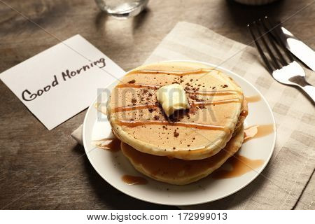Delicious breakfast and GOOD MORNING greeting note on wooden table closeup