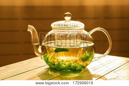 Glass teapot with herbal tea on wooden table