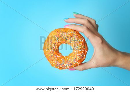 Woman holding delicious donut on color  background