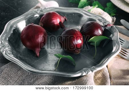 Silver bowl with red onion on gray table, closeup