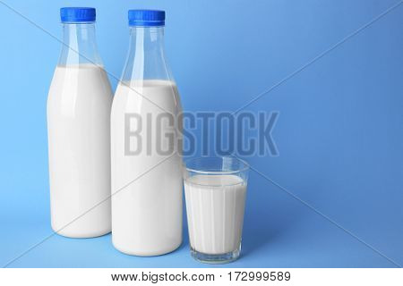 Bottles of tasty milk with glass on blue background