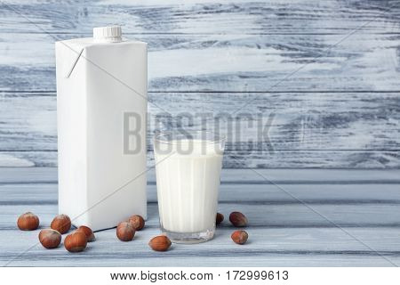 Carton box and glass of milk on wooden background