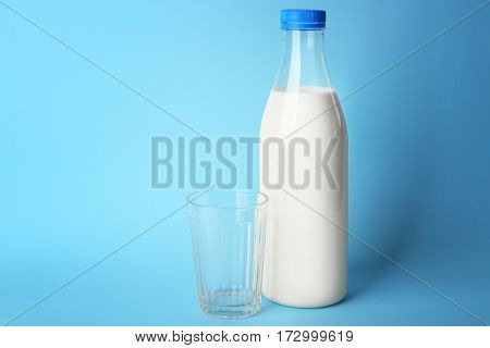 Bottle of tasty milk with glass on blue background
